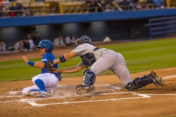 Matt Reynolds of the Las Vegas 51s slides safely past Steve Baron of the Tacoma Rainers into home plate Saturday at Cashman Field.  (Joshua Dahl/Las Vegas Review-Journal)