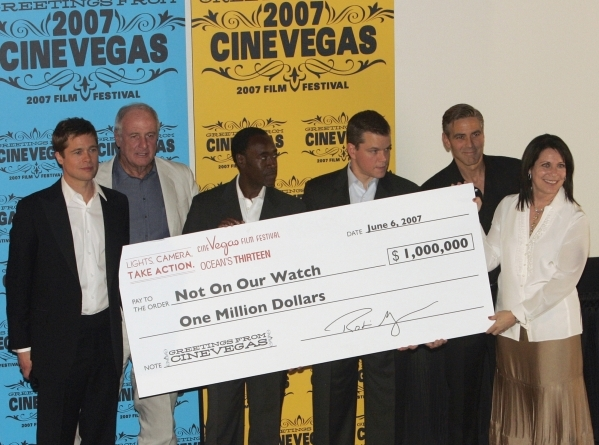 "CineVegas President Robin Greenspun (far right) presents an oversized check to the founders of Not On Our Watch during the CineVegas film festival opening night premiere of ""Ocean's Thi ..."