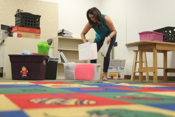 Alyssa Horton unpacks boxes in her kindergarten classroom at Piggott Elementary School, 9601 Red Hills Road, Aug.  3. The school has 702 students in its projected enrollment this year. (James Tens ...