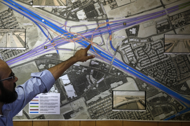 Resident engineer Abid Sulahria shows a map of the ultimate build out of the Centennial Bowl Interchange improvement project at his field office near Interstate U.S. 95 and the westbound 215 Beltw ...