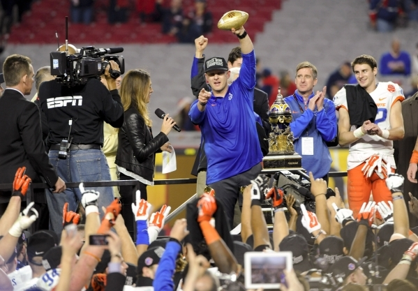 Dec 31, 2014; Glendale, AZ, USA; Boise State Broncos head coach Bryan Harsin celebrates with the Fiesta Bowl Trophy after defeating the Arizona Wildcats in the 2014 Fiesta Bowl at Phoenix Stadium. ...