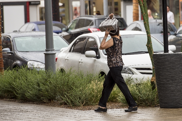 A woman uses her purse to shield herself from the rain as she walks through Downtown Summerlin in Las Vegas on Saturday, August 1, 2015. (Joshua Dahl/Las Vegas Review-Journal)