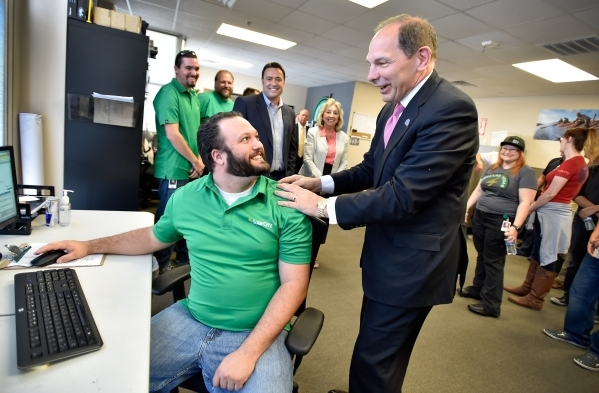 Veterans Affairs Secretary Robert McDonald, right, surprises John Robb at his desk after McDonald arrived for a visit to a SolarCity warehouse in North Las Vegas on Tuesday, Aug. 4, 2015. McDonald ...