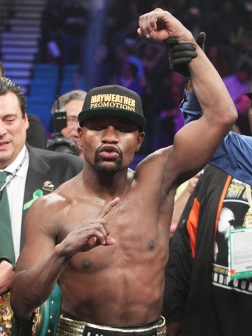 Floyd Mayweather Jr.'s arm is raised by referee Kenny Bayless after his unanimous decision over Manny Pacquiao in their welterweight title unification fight May 2 at the MGM Grand Garden. Ma ...