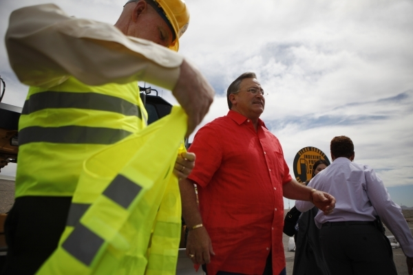 Clark County Commissioner Larry Brown, left, and Las Vegas Mayor Pro Tem Steve Ross participate during the groundbreaking ceremony for the Centennial Bowl Interchange improvement project at a cons ...
