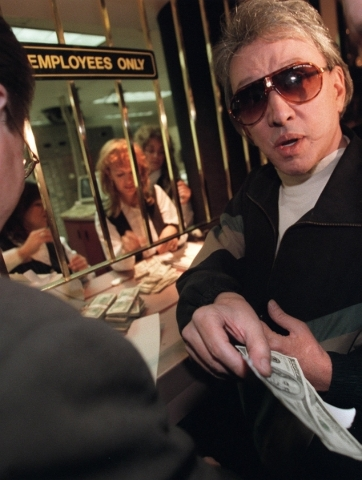 Bob Stupak wasn't just a casino owner, he also was a bettor. Here, in an undated photo, he hands out $200 to place a two-number keno bet while a Binion's Horseshoe cashier counts out his money ...