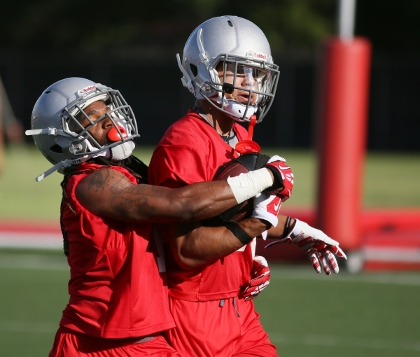 UNLV defensive back Jay'Onn Myles, left, grabs defensive back Dominique Fenstermacher during a training camp drill Aug. 7 at Rebel Park. Myles, a highly touted junior college transfer, worke ...