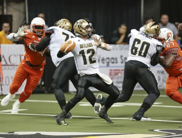 Las Vegas Outlaws quarterback Sean Brackett (12), prepares to make a pass while team mates Terrence Campbell (60), and  Will Wright (72) block defenders, during a football game between the Las Veg ...