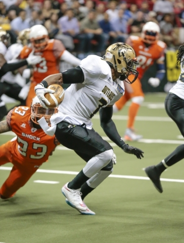 Las Vegas Outlaws Ray Little (7) looks for an opening through through other players, while being grabbed by Spokane Shocks player Jeff Richards (23)   during a football game between the Las Vegas  ...