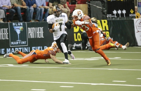 Las Vegas Outlaws, Ray Little (7) pushes away Spokane Shocks player Jeff Richards (23), as he runs the ball up the field from a kick off return during a football game between the Las Vegas Outlaws ...