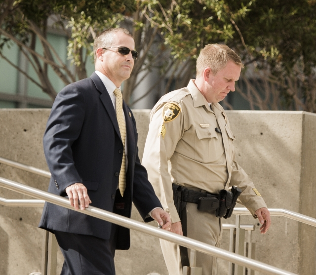 FBI Agent Michael Elliott ,left, and  Las Vegas police Sgt. Robert Whiteley, lead investigators in the HOA fraud case, walk down the steps of the Lloyd D. George U.S. Courthouse on Thursday, Aug.  ...