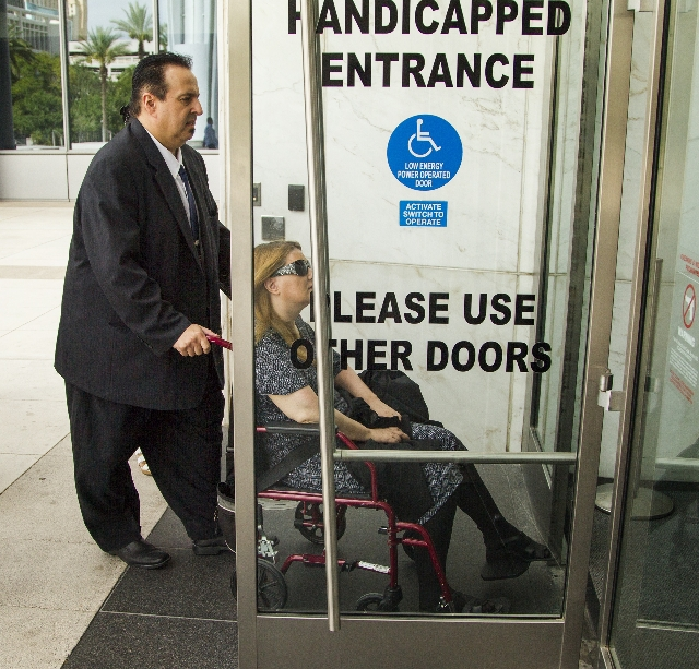 Leon Benzer, left, pushes  his ex-wife Karen in a wheelchair at  Lloyd D. George U.S. Courthouse Thursday, Aug. 6, 2015  before his sentencing. Benzer, the mastermind of the scheme to take over an ...