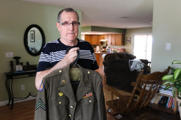 Wayne Rudolph poses with his father's jacket he wore during WWII on Wednesday, August 5, 2015. Rudolph's father Francis served in World War II and saw the bombing of Hiroshima, which w ...