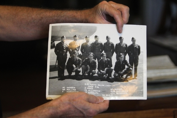 Wayne Rudolph points to a photo of his father Francis from when he was in WWII on Wednesday, August 5, 2015. Rudolph's father Francis served in World War II and saw the bombing of Hiroshima, ...