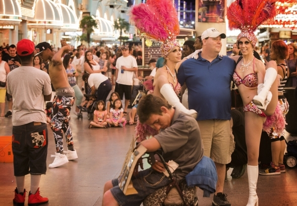 Women dressed in colorful showgirl costumes, at right, mingle with a visitor to the Fremont Street Experience. The city is considering an ordinance proposal that would control where buskers can pe ...