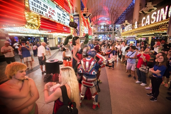 Crowds gather to watch buskers at the Fremont Street Experience in downtown Las Vegas. Costumed characters and other performers line the street in hopes of receiving trips from tourists. (Jeff Sch ...