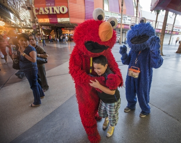 Memo Jay, dressed in an Elmo outfit, hugs a boy at the  Fremont Street Experience while a Cookie Monster character watches. (Jeff Scheid/Las Vegas Review-Journal)