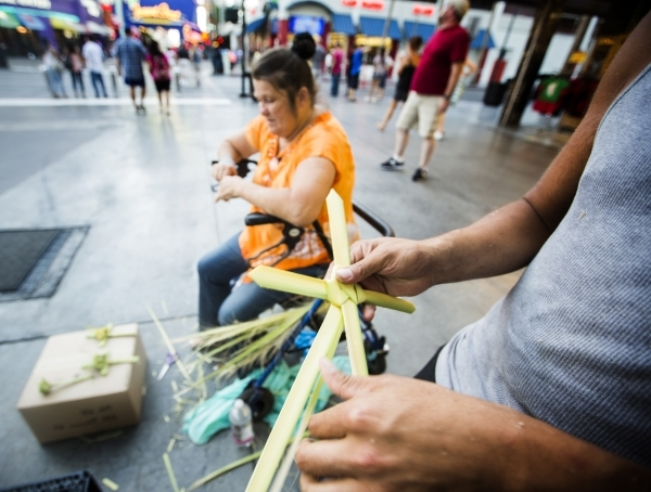 Buskers Jennie, left, and Nino, who declined to give last names, make ornamental pieces for a donation under the Fremont Street Experience canopy in downtown Las Vegas. (Jeff Scheid/Las Vegas Revi ...