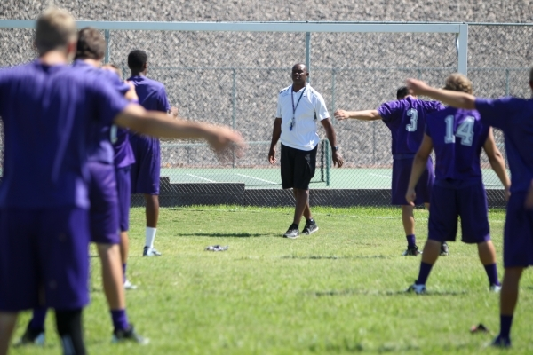 Former UNLV and NFL star Randall Cunningham, Silverado High School's football coach, watches his players Monday during stretches. (Erik Verduzco/Las Vegas Review-Journal)
