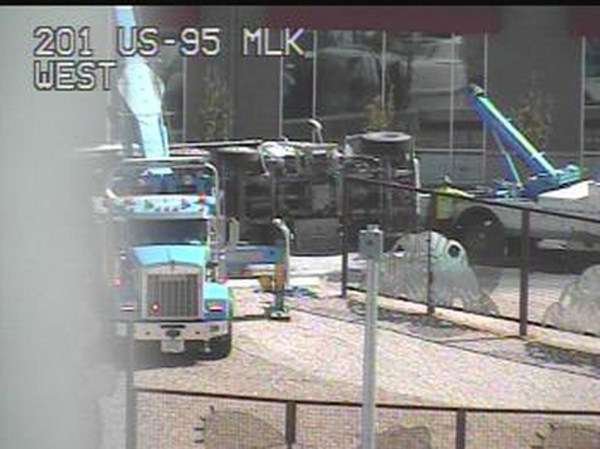Traffic cams show tow trucks attempting to upright a cement truck that overturned on Friday, Aug. 7, 2015, blocking the on-ramp from Martin Luther King Boulevard to southbound I-15. (NDOT)