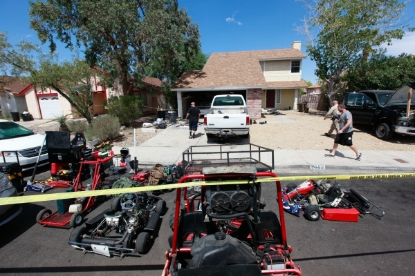 Las Vegas police officers investigate the home belonging to brothers Hugo and Frances Carbajal, who were both arrested on felony burglary charges, near Paradise and Warm Springs roads Friday. Vari ...