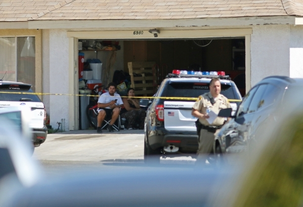 People sit in a garage at a home located in the 6900 block of Berkshire Place Friday, Aug. 7, 2015, in Las Vegas. Police checking reports of a broken window shot and killed a man who lunged at off ...