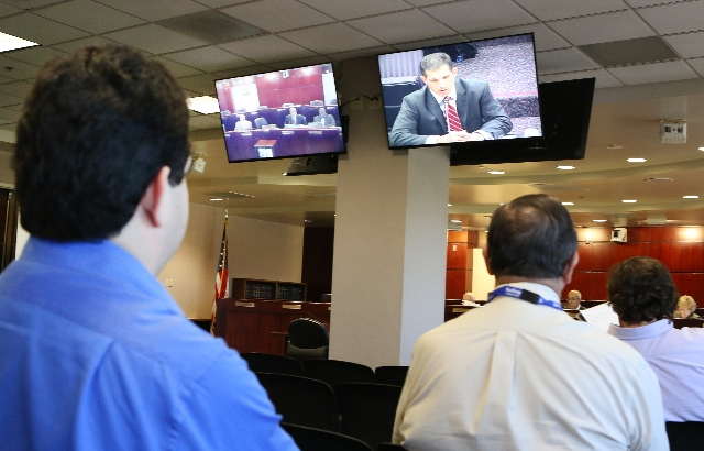 People watch as Andrew MacKay, chairman at Nevada Transportation Authority, right, speaks via video conference during a legislative hearing on Uber-related legislation at Grant Sawyer Building Mon ...