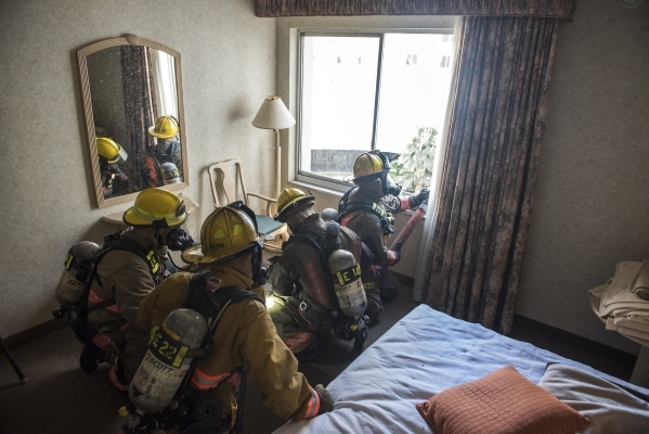 Clark County and Henderson firefighters learn to communicate and work in tight quarters during a joint high-ris exercise at the now closed Rivier on Monday. (Martin S. Fuentes/Las Vegas Review-Jou ...