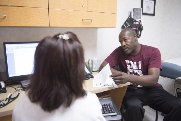 Anthony Howard, right, speaks with nurse practitioner Yvette Alto-Buenaflor at CVS pharmacy's Minute Clinic at 1825 E. Warm Springs Road. (Jason Ogulnik/Las Vegas Review-Journal)