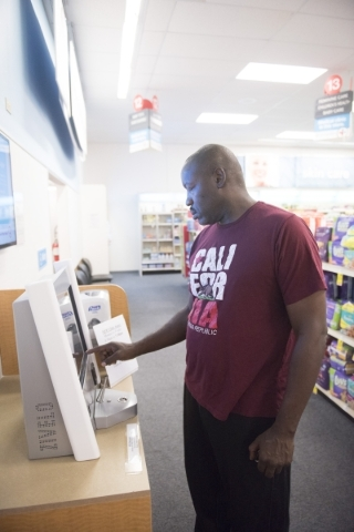 Anthony Howard signs up for an appointment at the self check-in kiosk at CVS pharmacy's Minute Clinic. (Jason Ogulnik/Las Vegas Review-Journal)