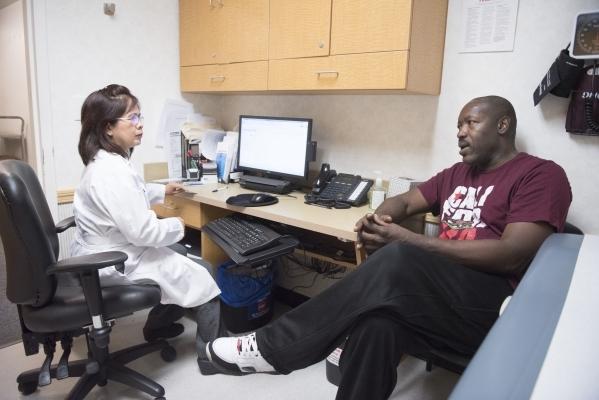 Anthony Howard, right, speaks with nurse practitioner Yvette Alto-Buenaflor at CVS pharmacy's Minute Clinic. (Jason Ogulnik/Las Vegas Review-Journal)