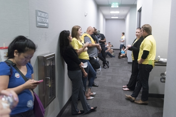 Rooftop solar advocates and workers are shown waiting for spaces to open up in the meeting room at the Public Utilities Commission West Diablo Road office in Las Vegas, Wednesday, Aug. 12, 2015. ( ...