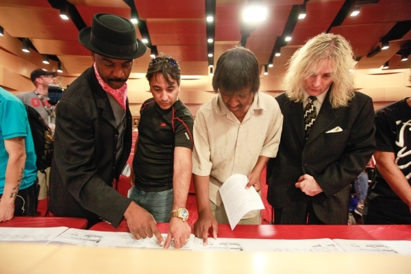 """Scarlet Ray Watt, from left, """"Olly,"""" Stanley Washington, and Zenon Skyy look over a map showing proposed street performer zones during a public meeting about the Fremont Street performer ..."""