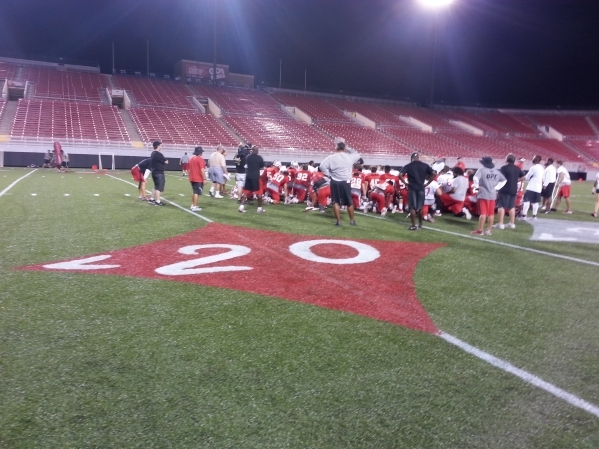 "UNLV players gather around coaches after they practiced on the newly decorated turf at Sam Boyd Stadium on Wednesday night. The field has a Las Vegas casino look with a take on the famous ""We ..."
