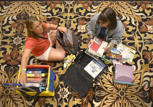 Sisters Jody Mancuso, left, from Dean Allen Elementary School and Mindy Walter from Palo Verde High School look through school supplies donated by MGM Resorts employees at The Mirage in Las Vegas  ...
