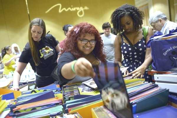 From left, Amy Wolfe, Anielka Lopez and Ebonee Coe, all from Park Elementary School, along with thousands of Clark County School District teachers, look through school supplies donated by MGM Reso ...