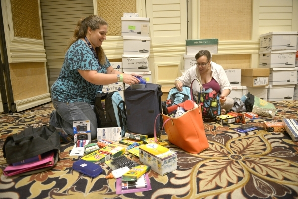 Jill Vecchio, left, and Ashlei Livingston, both from Doris Hancock Elementary School, look through their supplies along with thousands of Clark County School District teachers. The free school sup ...