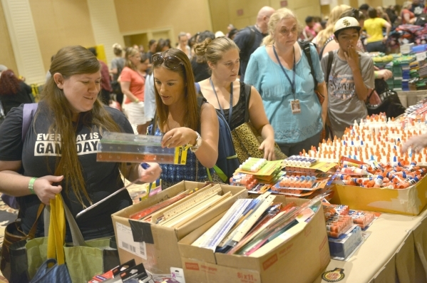 From left, Katrina Miller and Tina LeRoy, both from Clyde Cox Elementary, wait in line with thousands of Clark County School District teachers for free school supplies donated by MGM Resorts emplo ...