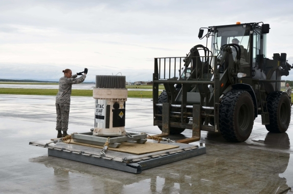 Tech. Sgt. Rebecca Morin, 354th Logistics Readiness Squadaron noncommissioned officer in charge of air terminal operations at Eielson AFB, Alaska, gives hand signals to forklift driver Staff Sgt.  ...