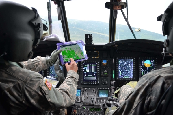 Chief Warrant Officer 3 Rafael Caldeira, left, uses a tablet to show current weather conditions to fellow pilot Chief Warrant Officer 4 Dave Lawson, as the two soldiers fly their CH-47 Chinook fro ...