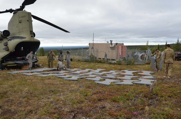 Airmen from the Air Force Technical Applications Center's Detachment 460 at Eielson AFB and Soldiers from B Company, 1-52 Aviation Brigade at Ft. Wainwright lay several yards of modular surf ...
