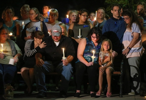 Grief-stricken family members of Carson City Sheriff's Deputy Carl Howell, who was killed in the line of duty early Saturday while responding to a domestic dispute, attend a candlelight vigi ...