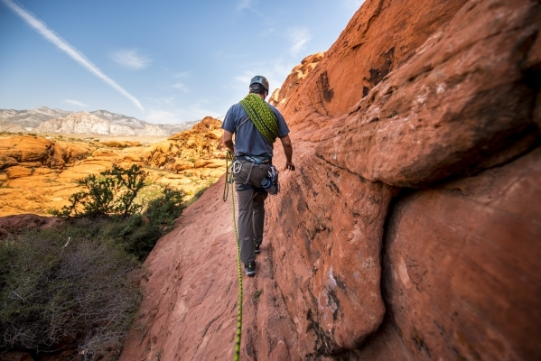 Doug Foust walks along a cliff while rock climbing at Red Rock Canyon in Las Vegas on Tuesday, Aug. 18, 2015. (Joshua Dahl/Las Vegas Review-Journal)