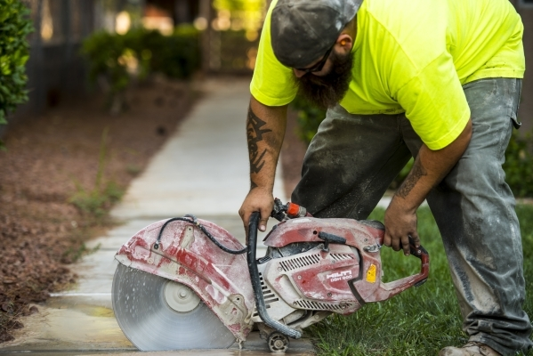 Chris Poff cuts a sidewalk at Spanish Palms on South Rainbow Boulevard during construction of a park in the complex. (Joshua Dahl/Las Vegas Review-Journal)