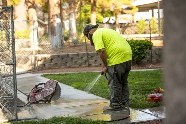 Chris Poff hoses off a sidewalk at Spanish Palms during construction of a park in the complex. (Joshua Dahl/Las Vegas Review-Journal)