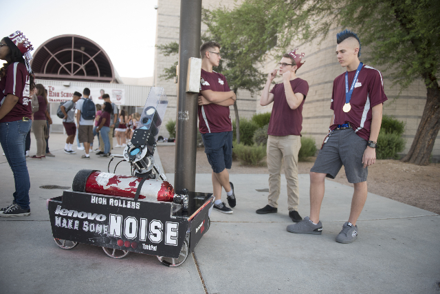 Members of the robotics club at Cimarron-Memorial High School, from left, Chris Woerner, senior, Max Reed, senior, and Brendan Mulcahy, senior, stand next to their T-shirt launching robot before c ...