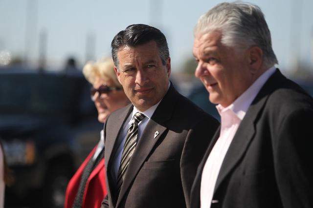 Nevada officials, from left, Las Vegas Mayor Carolyn Goodman, Gov. Brian Sandoval and Clark County Commissioner Steve Sisolak walk on the tarmac at McCarran International Airport in Las Vegas Mond ...