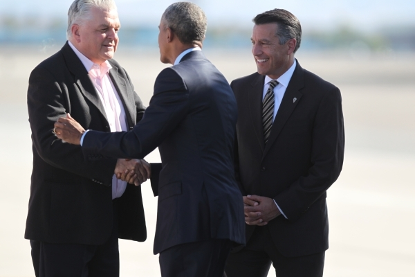 Nevada officials, County Commissioner Steve Sisolak, left, and Gov. Brian Sandoval, right, welcome President Barack Obama on the tarmac at McCarran International Airport in Las Vegas Monday, Aug.  ...