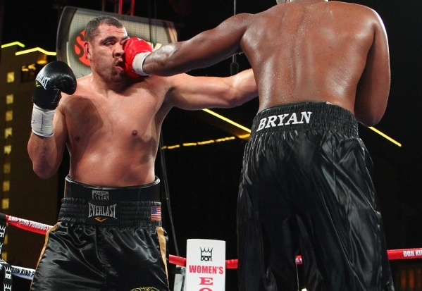 Derric Rossy, left, takes a hit from Trevor Bryan during their NABF heavyweight title fight Friday at the Downtown Las Vegas Events Center. Bryan (16-0) won a 10-round unanimous decision. CHASE ST ...