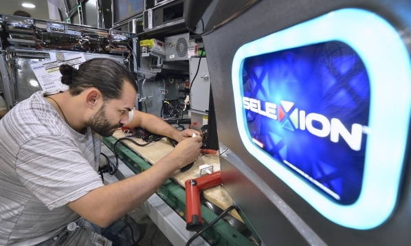 Assembler Eric Trejo checks a switch on the assembly line at Konami Gaming in Las Vegas on Friday, Aug. 28, 2015. (Bill Hughes/Las Vegas Review-Journal)